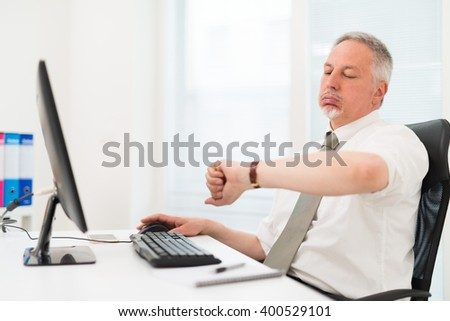 Bored businessman looking at his watch - stock photo