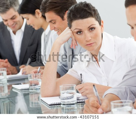 Bored businesswoman at a presentation with her colleagues - stock photo