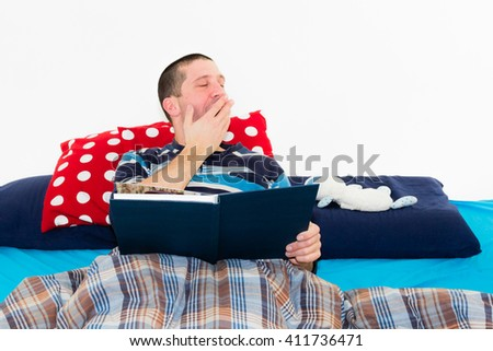 Bored caucasian man reading a book alone on the bed