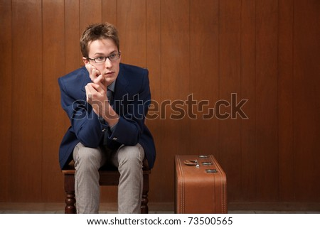 Bored Caucasian traveller sitting in a room - stock photo