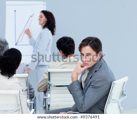 Bored charming businessman at a presentation with his colleagues - stock photo