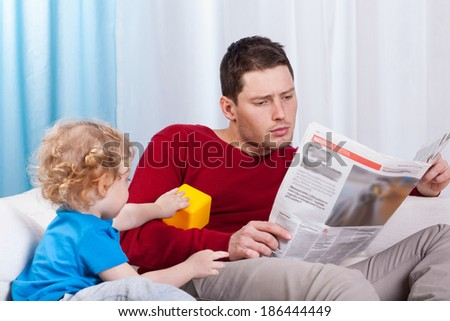 Bored child looking at father reading newspaper - stock photo
