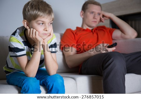 Bored child with his father sitting and watching tv on the sofa - stock photo