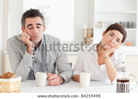 Bored couple drinking coffee in a kitchen - stock photo