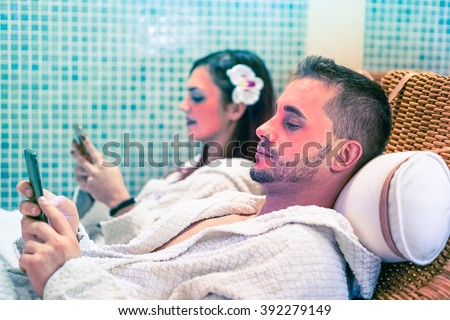 Bored couple phone addicted in spa is lying on sauna bed - Mutual disinterest between man and young woman in wellness center - Fake facial mask with pop style colors for a  funny drama marriage scene - stock photo
