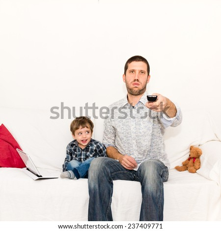 Bored father watching tv with a smile baby teases him - stock photo