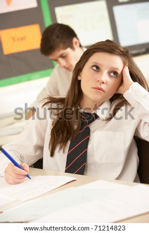 Bored Female Teenage Student Studying In Classroom - stock photo