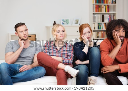 Bored group of multiracial friends relaxing at home sitting in a row on a comfortable sofa watching something off screen to the right with glum expressions - stock photo
