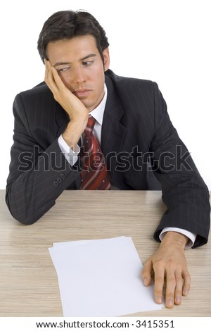 Bored, handsome businessman. Seating behind desk. White background, front - stock photo