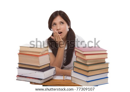 bored High school or college Latina female student sitting by the desk with pile of books in front of her