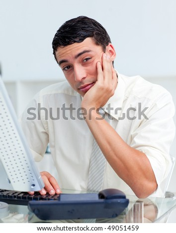 Bored Hispanic businessman at his desk in the office - stock photo