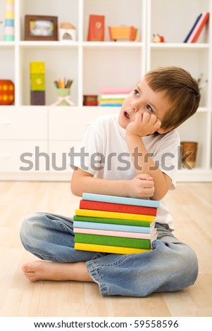 Bored kid with lots of school books daydreaming while sitting on the floor - stock photo