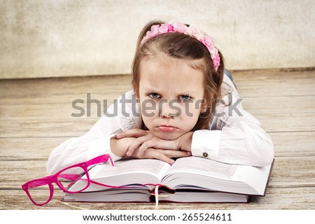 Bored little girl with books - stock photo
