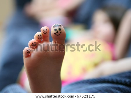 Bored little lying on couch girl showing the bottom of her foot with smiley faces drawn on her toes - stock photo