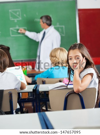 Bored little schoolgirl sitting at desk with teacher teaching geometry in classroom - stock photo