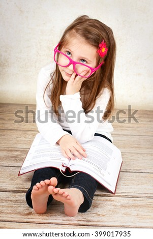 Bored little schoolgirl wearing glasses and reading book - stock photo