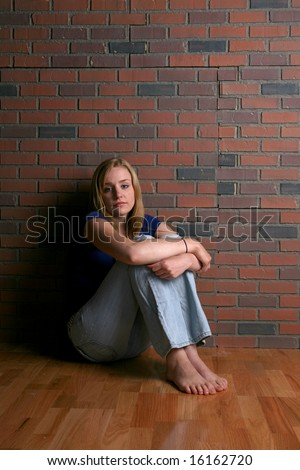 bored looking sad woman sitting with knees up - stock photo