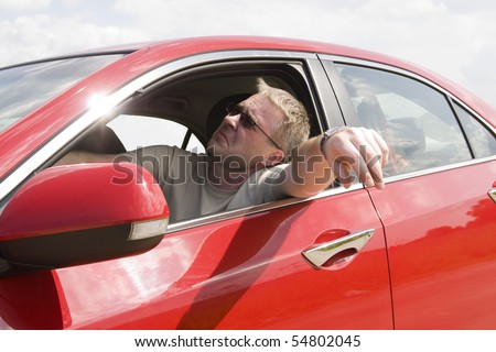 bored man in red car - stock photo