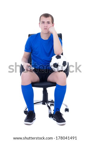 bored man in uniform sitting with remote control and watching soccer game isolated on white background - stock photo