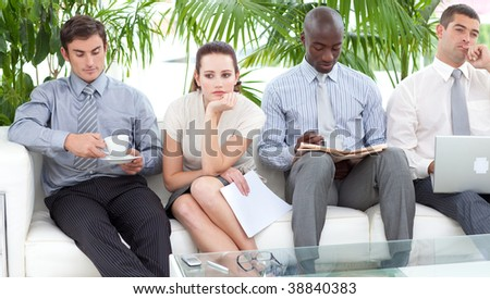 Bored multi-ethnic business people sitting on a sofa waiting for an interview - stock photo