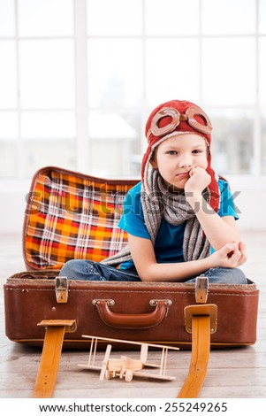 Bored of playing. Bored little boy in pilot headwear and eyeglasses holding hand on chin and looking at camera while sitting inside of briefcase at home  - stock photo