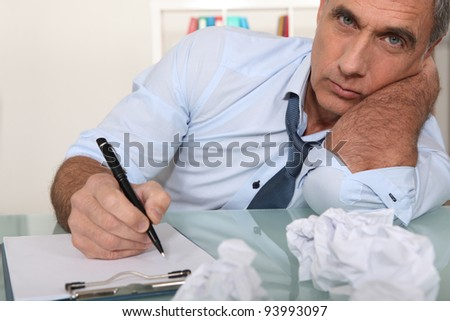 Bored office worker writing - stock photo