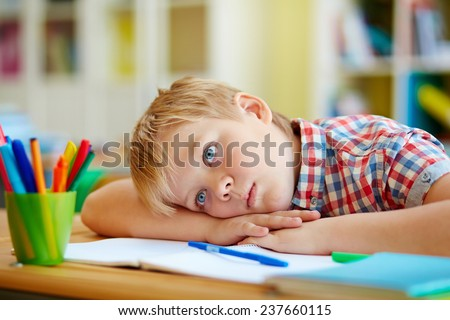 Bored or pensive schoolboy lying on desk - stock photo
