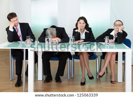 Bored panel of professional judges or corporate interviewers lounging around on a table napping as they wait for something to happen - stock photo