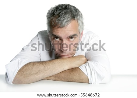 bored senior businessman on table desk hands crossed white background - stock photo