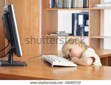 Bored small kid with computer in classroom - stock photo