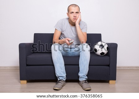 bored soccer fan watching game on tv at home - stock photo