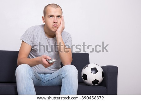 bored soccer fan with ball watching game on tv at home - stock photo