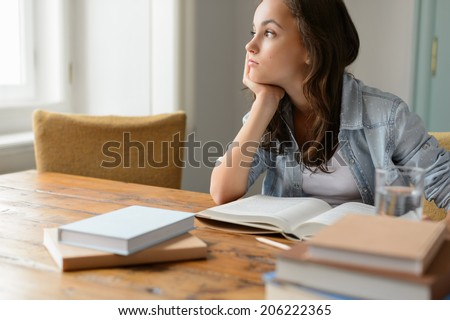 Bored student girl sitting home living room looking away read book - stock photo