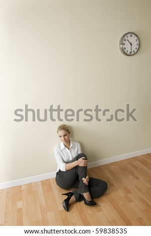 Bored/Tired businesswoman sitting on the floor - stock photo