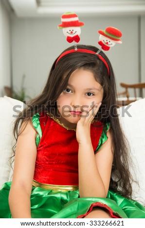 Bored tired grumpy little girl in Christmas dress - stock photo