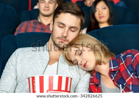 Bored to sleep. Closeup shot of a beautiful young couple sleeping during movies in a local cinema