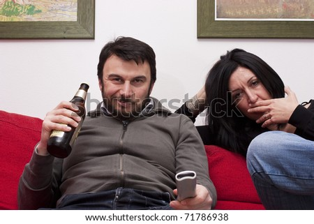 Bored Wife and Arrogant Husband Watching Television - stock photo