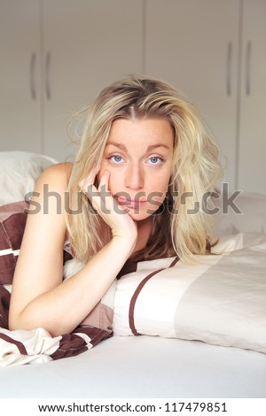 Bored woman confined to her bed while recouperating from an illness looking at the camera with a depondent expression