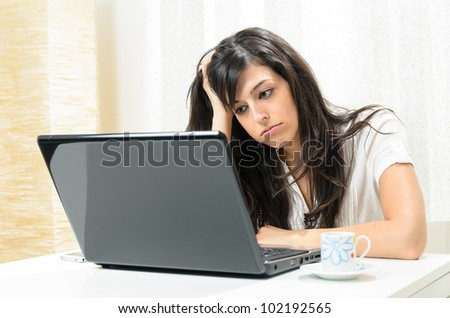 Bored woman homework. Tired beautiful hispanic girl with laptop computer indoor, - stock photo