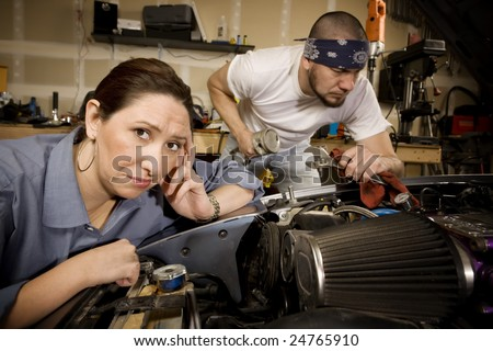 Bored woman leaning on car with male mechanic ignoring her in background - stock photo