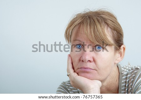 Bored woman looking into the camera - stock photo