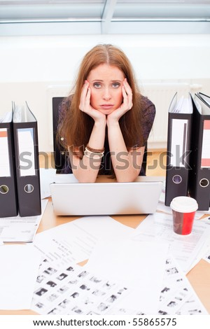 bored woman sitting at the table staring at the wall - stock photo