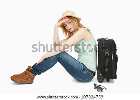 bored woman sitting near a suitcase against white background - stock photo