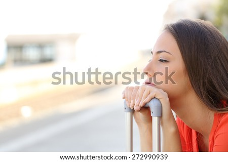 Bored woman waiting for delayed transportation in a train station - stock photo