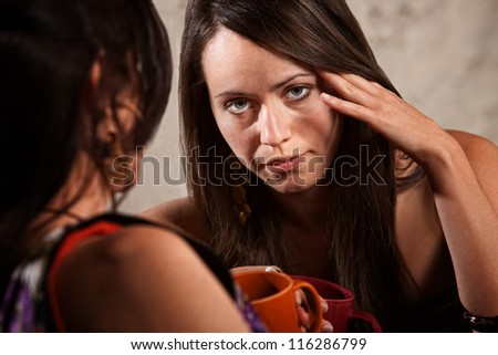 Bored woman with fingers on head listening to friend - stock photo