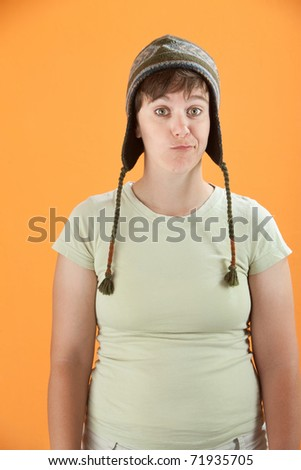 Bored woman with sock monkey hat on orange background - stock photo