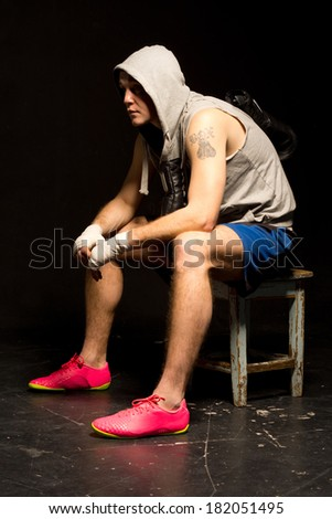 Bored young boxer waiting for his match sitting on a wooden stool in a hoodie with his gloves dangling round his neck, side view against a dark background - stock photo