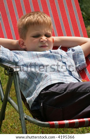 Bored young boy is sitting in striped chair
