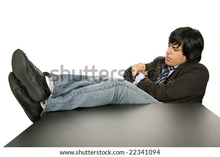 bored young business man on a desk, isolated on white