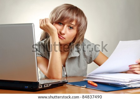 Bored young businesswoman at her desk against  grey background